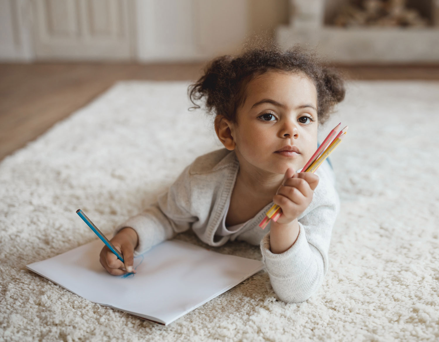 little girl writing on rug